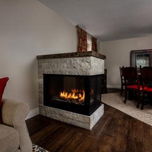 トロントの中くらいのトランジショナルスタイルのおしゃれなLDK (グレーの壁、無垢フローリング、両方向型暖炉、積石の暖炉まわり、茶色い床) の写真