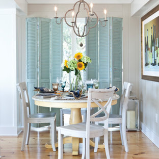 Cette image montre une salle à manger marine avec un mur gris, un sol en bois clair, un sol beige et du lambris de bois.