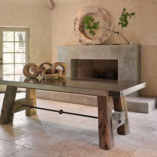 Réalisation d'une salle à manger champêtre fermée et de taille moyenne avec un mur beige, un sol en carrelage de céramique, une cheminée standard, un manteau de cheminée en béton et un sol beige.