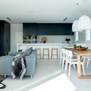 This is an example of a large coastal open plan dining room in Perth with grey walls and white floors.