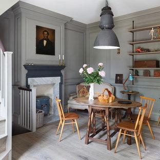 Modelo de comedor clásico, pequeño, con suelo de madera en tonos medios, estufa de leña, marco de chimenea de piedra y paredes grises