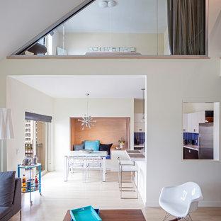 Imagen de comedor actual, abierto, con paredes blancas y suelo de madera clara