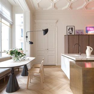 Cette photo montre une salle à manger ouverte sur la cuisine chic avec un mur blanc, un sol en bois clair et un sol beige.