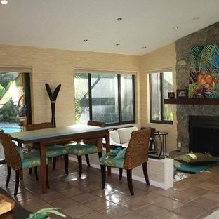 タンパの中サイズのトロピカルスタイルのおしゃれなLDK (茶色い壁、標準型暖炉、石材の暖炉まわり、茶色い床) の写真