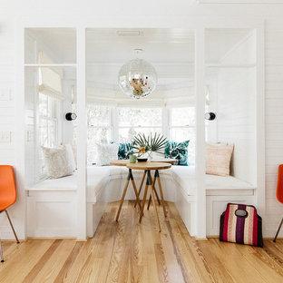 Ejemplo de comedor marinero, pequeño, abierto, sin chimenea, con paredes blancas, suelo de madera clara y suelo marrón