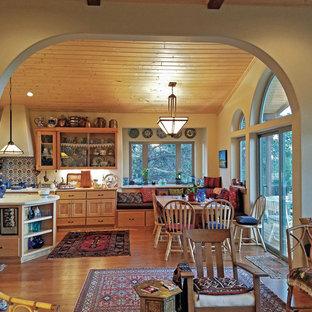 Foto de comedor de cocina de estilo americano, de tamaño medio, con paredes amarillas y suelo laminado