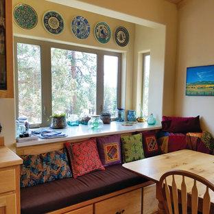 Modelo de comedor de cocina de estilo americano, de tamaño medio, con paredes amarillas y suelo laminado