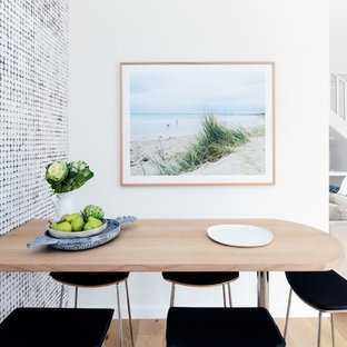 Photo of a large beach style dining room in Sydney with white walls, light hardwood floors and beige floor.