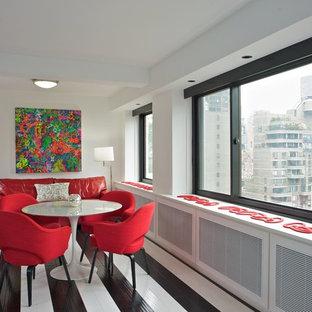 Cette image montre une salle à manger design fermée et de taille moyenne avec un sol en bois peint, un mur blanc, aucune cheminée et un sol multicolore.