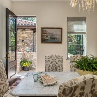 Immagine di una grande sala da pranzo aperta verso la cucina mediterranea con pareti beige, pavimento in terracotta, nessun camino e pavimento rosa