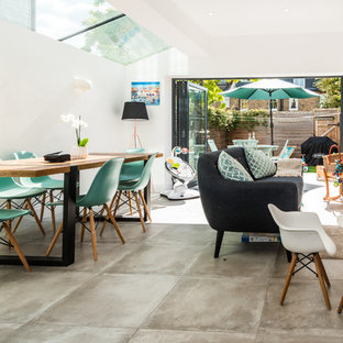 Photo of a medium sized contemporary dining room in London with white walls and beige floors.