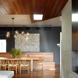 Cette image montre une salle à manger ouverte sur le salon design avec un mur noir, un sol en bois brun, un sol marron, un plafond en bois et du lambris de bois.