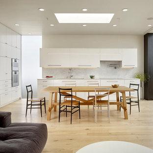 Idee per una sala da pranzo aperta verso la cucina contemporanea di medie dimensioni con pareti bianche, pavimento in laminato e pavimento marrone