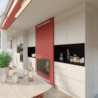 Ispirazione per una sala da pranzo aperta verso la cucina moderna di medie dimensioni con pareti beige, pavimento con piastrelle in ceramica, camino classico, cornice del camino in intonaco e pavimento multicolore