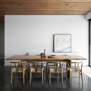 Inspiration for a contemporary dining room in Melbourne with white walls, concrete floors, no fireplace and grey floor.