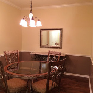 Small trendy dark wood floor enclosed dining room photo in Houston with yellow walls