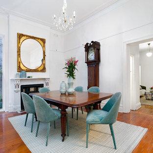 Exemple d'une salle à manger victorienne avec un mur blanc, un sol en bois brun, une cheminée standard et un sol marron.