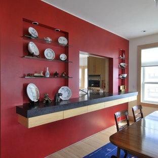 Imagen de comedor actual, abierto, sin chimenea, con paredes rojas y suelo de bambú