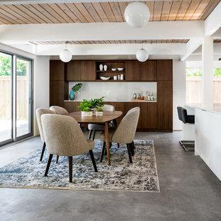 Idee per una sala da pranzo aperta verso la cucina moderna di medie dimensioni con pareti bianche, pavimento in cemento e pavimento grigio