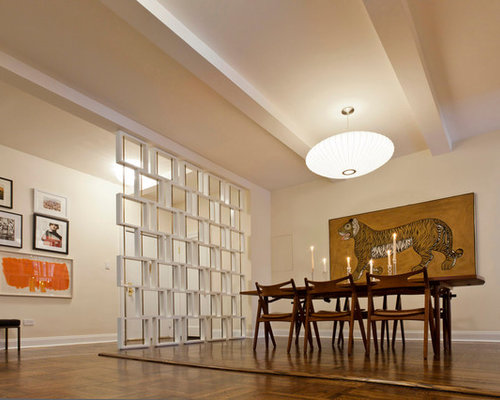 Example Of A Minimalist Dining Room Design In New York With Beige Walls And Dark Hardwood