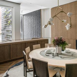 Imagen de comedor minimalista, de tamaño medio, abierto, con paredes blancas, suelo de madera en tonos medios, chimenea tradicional y marco de chimenea de madera