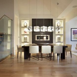 Esempio di una sala da pranzo aperta verso il soggiorno minimalista di medie dimensioni con pareti bianche, parquet chiaro, camino lineare Ribbon e cornice del camino in cemento