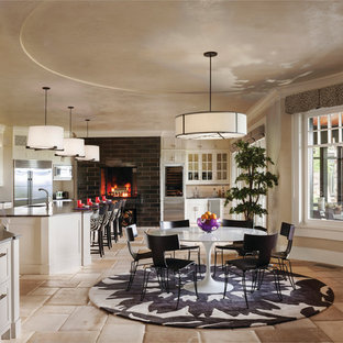 Esempio di una sala da pranzo aperta verso la cucina contemporanea di medie dimensioni con pareti beige, pavimento beige, camino sospeso e cornice del camino piastrellata