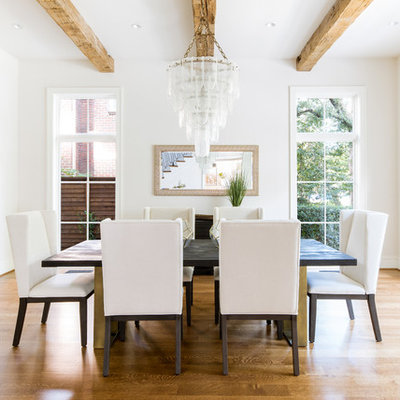 Transitional medium tone wood floor enclosed dining room photo in Dallas with white walls