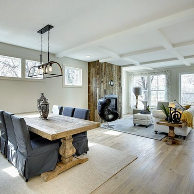 Great room - mid-sized cottage light wood floor great room idea in Minneapolis with white walls, a standard fireplace and a wood fireplace surround