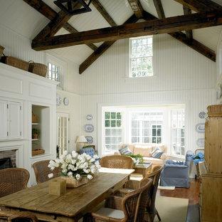 Esempio di una sala da pranzo aperta verso il soggiorno tradizionale di medie dimensioni con pareti bianche, pavimento in legno massello medio, camino classico e cornice del camino in mattoni
