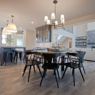 Idée de décoration pour une salle à manger ouverte sur le salon avec un sol en vinyl, un manteau de cheminée en pierre de parement et un sol gris.