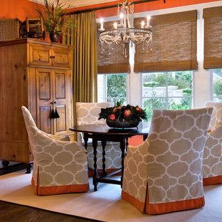 Exemple d'une salle à manger ouverte sur la cuisine chic de taille moyenne avec un mur orange, un sol marron et un sol en bois foncé.