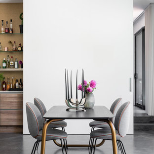 Eclectic open plan dining in Perth with white walls, concrete floors and grey floor.