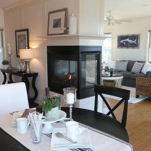Esempio di una sala da pranzo aperta verso la cucina costiera di medie dimensioni con pareti bianche, parquet chiaro, camino bifacciale e cornice del camino in metallo
