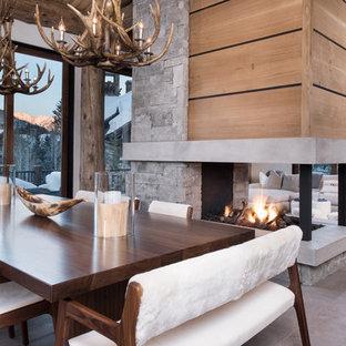 Стильный дизайн: гостиная-столовая среднего размера в современном стиле с бежевыми стенами, полом из сланца, двусторонним камином, фасадом камина из камня и серым полом - последний тренд