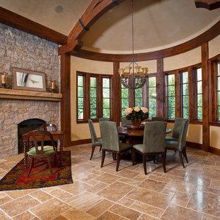 Diseño de comedor de cocina rústico, extra grande, con paredes beige, marco de chimenea de piedra, suelo de piedra caliza y chimenea tradicional