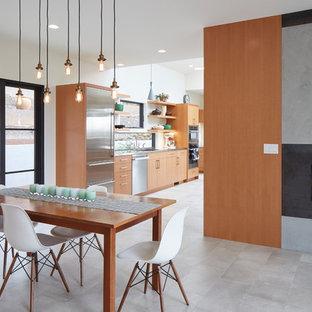 Imagen de comedor de cocina actual, de tamaño medio, con paredes blancas, suelo de baldosas de porcelana, chimenea de esquina, marco de chimenea de yeso y suelo gris