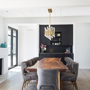 Ispirazione per una grande sala da pranzo aperta verso il soggiorno minimalista con pareti bianche, parquet chiaro, camino classico e cornice del camino in mattoni