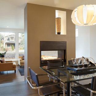 Ejemplo de comedor contemporáneo, de tamaño medio, abierto, con chimenea de doble cara, paredes beige, suelo de madera oscura, marco de chimenea de metal y suelo marrón