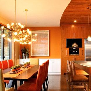 Immagine di un'ampia sala da pranzo aperta verso la cucina moderna con pareti arancioni, pavimento in sughero, camino sospeso, cornice del camino in legno e pavimento grigio