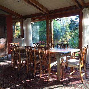 Ejemplo de comedor de cocina tradicional renovado, grande, con paredes rojas, suelo de pizarra, chimenea de doble cara, marco de chimenea de hormigón y suelo gris