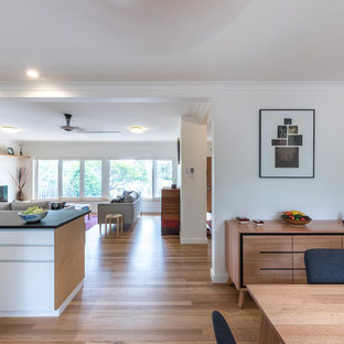 Exemple d'une salle à manger ouverte sur le salon tendance de taille moyenne avec un mur blanc, un sol en bois clair et un sol jaune.