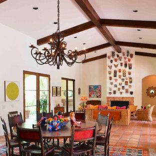 Modelo de comedor de estilo americano, grande, abierto, con paredes blancas, suelo de baldosas de terracota, chimenea tradicional, marco de chimenea de baldosas y/o azulejos y suelo rojo