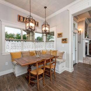 他の地域の中サイズのおしゃれなダイニングキッチン (グレーの壁、セラミックタイルの床、両方向型暖炉、レンガの暖炉まわり、茶色い床) の写真