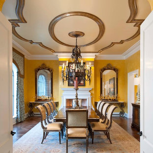 This is an example of a large mediterranean open plan dining room in Dallas with yellow walls, dark hardwood flooring and a standard fireplace.