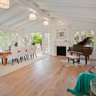 Modelo de comedor ecléctico, grande, abierto, con suelo de madera en tonos medios, paredes blancas, chimenea tradicional y marco de chimenea de madera
