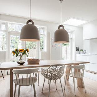 Esempio di una sala da pranzo scandinava con pareti bianche, parquet chiaro e nessun camino
