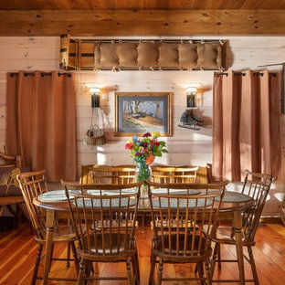 This is an example of a country separate dining room in Burlington with beige walls, medium hardwood floors and no fireplace.