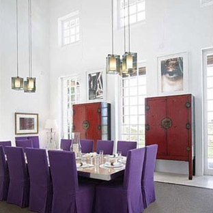 This is an example of a large tropical dining room in Miami with white walls.