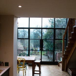 Foto di una grande sala da pranzo aperta verso la cucina industriale con pareti multicolore, pavimento in legno massello medio, pavimento marrone e pareti in mattoni